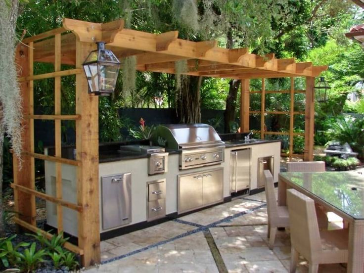 This pergola-style gazebo rests over the top of this stainless steel grill and outdoor kitchen area. The area is just below large willow trees, which drape foliage down over the grill.
