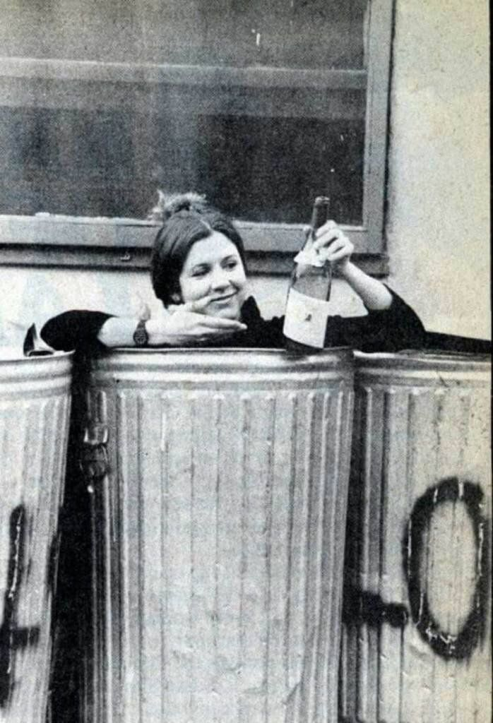Carrie Fisher in the trash with a bottle of wine, 1977.