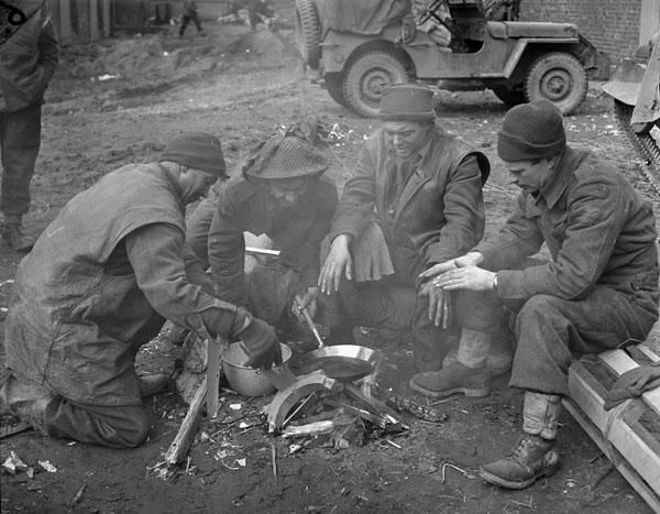 Infantrymen of The Argyll and Sutherland Highlanders of Canada cooking a meal and warming themselves around a fire in a barnyard near Veen, Germany, March 7th 1945.  (L-R): Privates Bob Fessay, G.J. Burt, K.L. McKenney and L.R. Young.  Photograph by Captain Jack H. Smith.