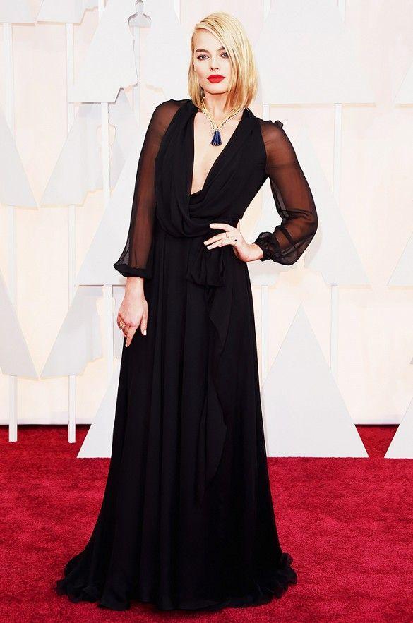 Margot Robbie in a low-cut, black Saint Lauren gown and Van Cleef & Arpels tassel necklace at the 2015 Oscars