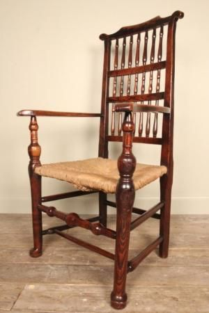 A charming and lovely example of a Fruitwood, Ash and Rush seated Cheshire country chair.  This large elbow chair having superb colour and patina throughout.  With a decorative spindle back and outswept shaped arms adjoined to the seat with turned uprights, terminating in pad feet.  Beautiful stretcher rails make this chair stable and strong, the rush seat in good condition. Good proportions and full or character.  English, Early 19th Century