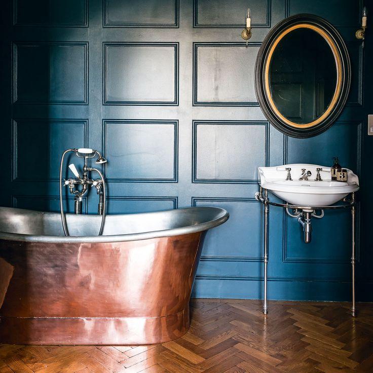 Bathroom - Deep blue walls, copper-plated freestanding bath, herringbone parquet  floors. #herringbone #copper