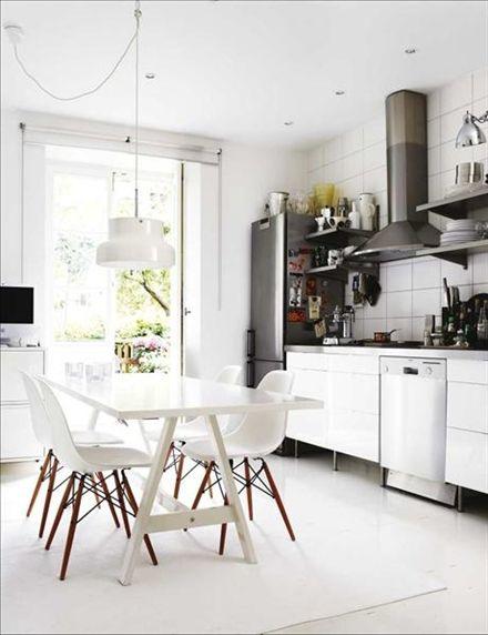 Köksbordet är Ikea PS som var i stavlimmad björk innan Jutta målade det vitt. Stolarna är Charles och Ray Eames klassiska Plastic sidechair och lampan Ateljé Lyktans Bumling. Ljuslyktor från från Staken&veken i Helsingborg. Hela köksinredningen är från Ikea utom metallhyllorna som är från Hyllteknik. Från köket kommer man direkt ut på en terrass mot en grönskande innergård.