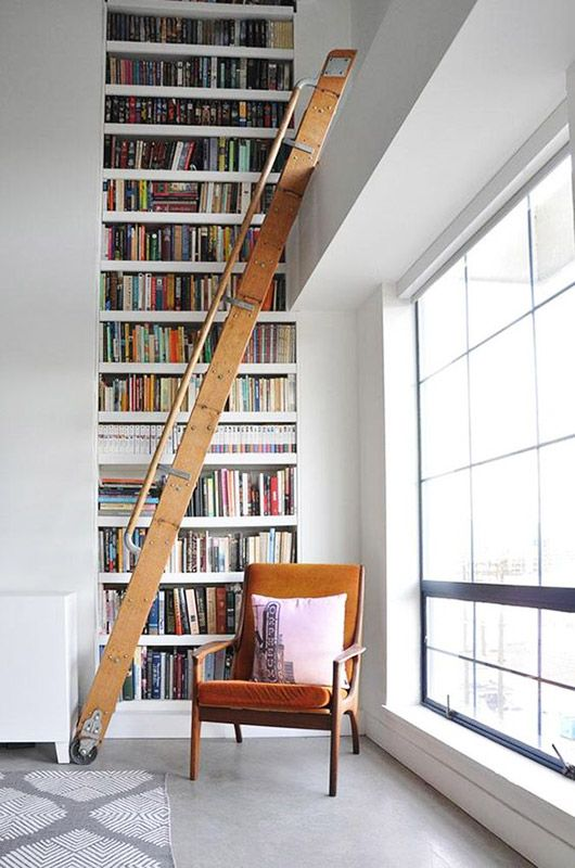 tall white built-in bookcase with wood rolling library ladder / sfgirlbybay