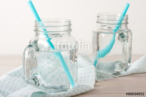 two glass jars of water with blue straws