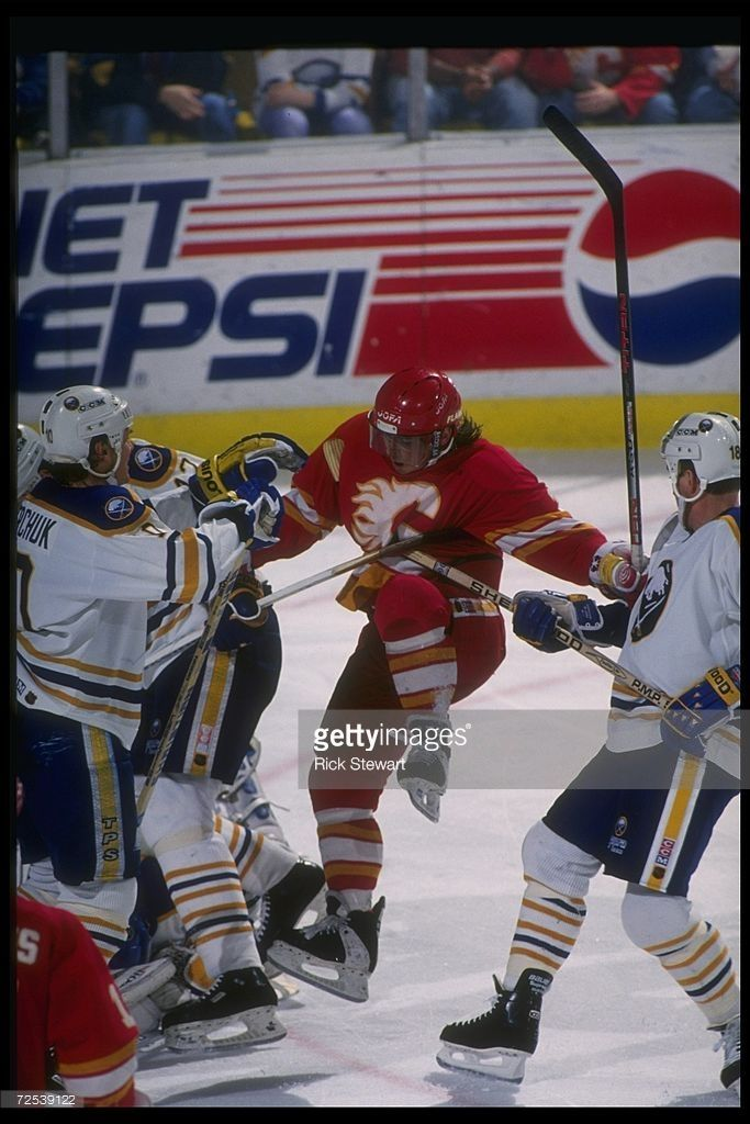 Rightwinger Theoren Fleury of the Calgary Flames (center) fights the Buffalo Sabres during a game at Memorial Auditorium in Buffalo, New York, 1994