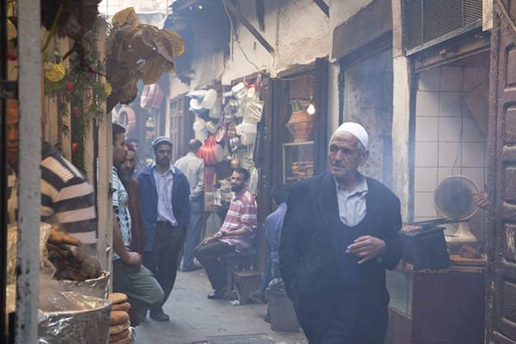 Man walking through alleyway lined with food stalls in Souq El Attarine.