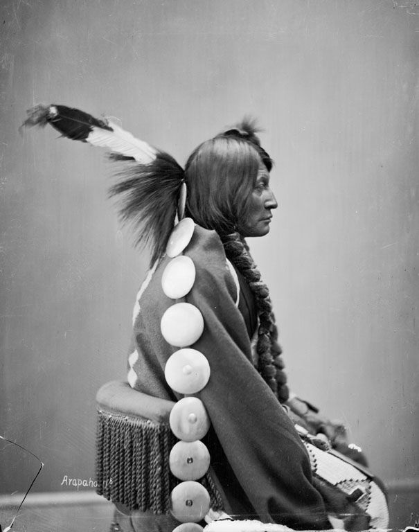 Arapaho Portrait (Profile) of Bi-Nan-Set (Big Mouth Hawk) or (Big Mouth) in Partial Native Dress with Headdress and Holding Pipe-tomahawk 1872