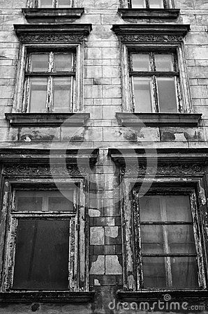 Four windows of an old creepy haunted abandoned house. Black and white version.