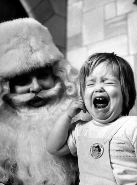 Ken Berends, a Santa Claus in training, looking bewildered at wailing little girl, during practice session for his Santa certificate during 5-day, 75dollar-course at Santa school to enable him to get Yuletide jobs at local department stores. ©Time. Photo by Alfred Eisenstaedt, 1961.