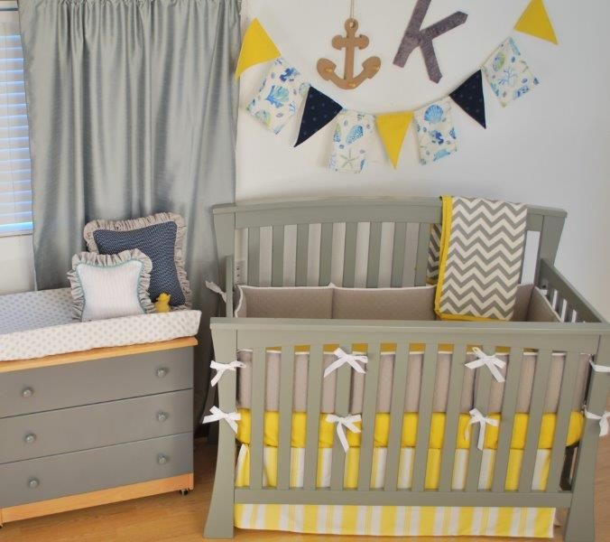 grey and bright yellow crib bedding with a pennant banner