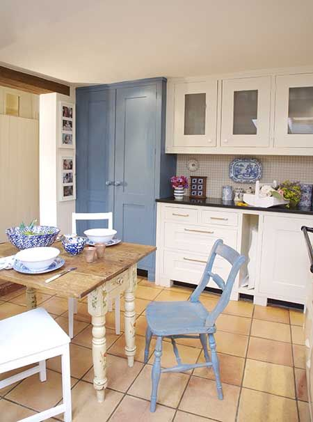 Blue Painted Chair At Breakfast Table In Centre Of Country Style Kitchen