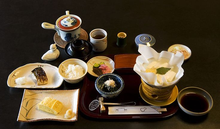 A traditional kaiseki 懐石 multi-course breakfast at Tamahan Ryokan, Kyoto. The dishes include roast mackerel, dashimaki (Japanese omelette, here Kansai style), rice, a paper pot (kami nabe) of yudofu over a small brasier, with soy sauce and toppings (negi and katsuobushi), tsukemono (cucumber, pickling melon, turnip) and green tea. In the black cup is miso soup.