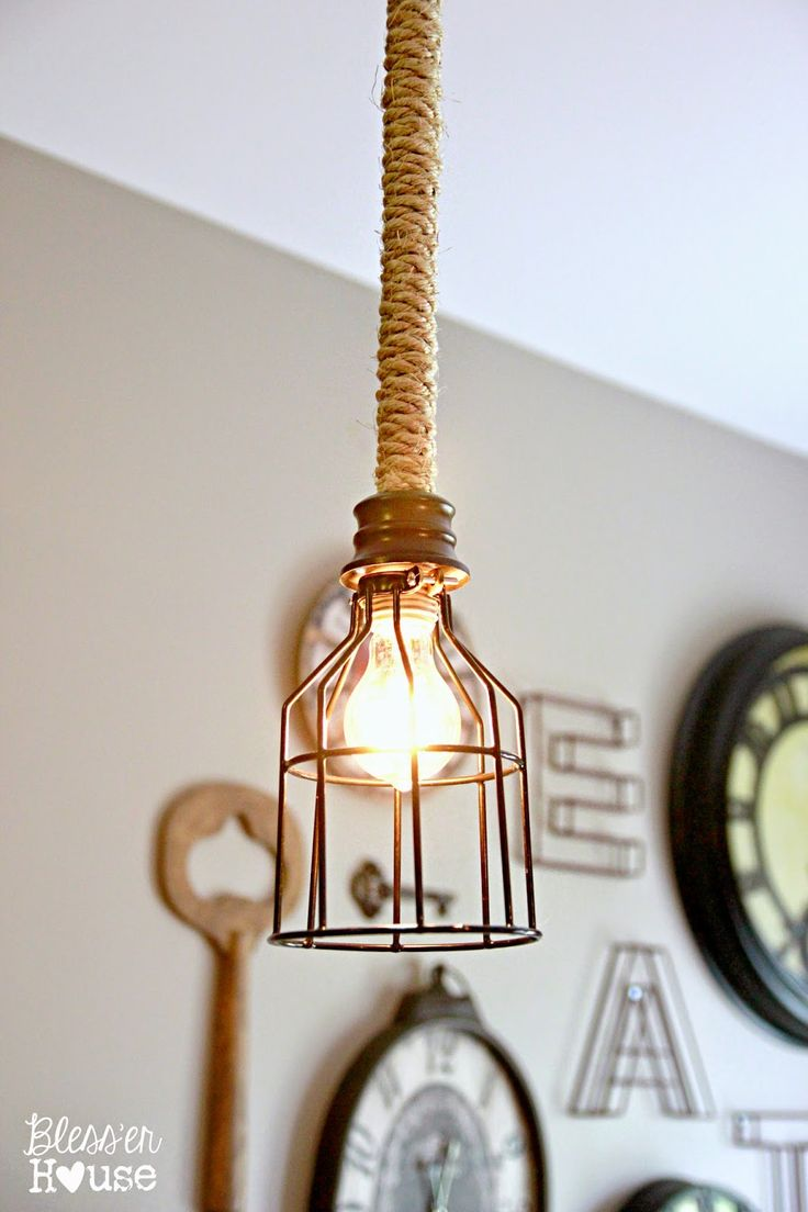 DIY:  How to Make this Industrial Pendant Light - using a plain pendant light fixture, spray paint, rope, glue and a great industrial wire shade - via Bless'er House