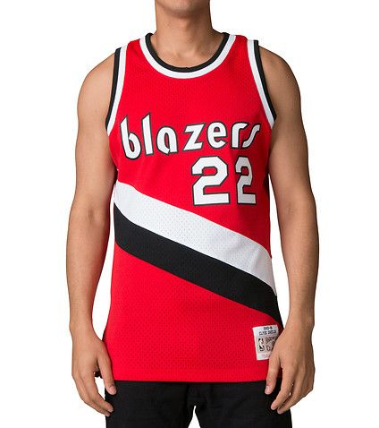 Clyde'The+Glide'+Drexler+is+one+the+game's+greatest+guards+and+known+for+his+high+flying+moves+to+the+basket.Rep+one+of+the+NBA's+Greatest+50+players+in+the+Mitchell+and+Ness+Swingman+Jersey.MITCHELL+AND+NESS+Embroidered+Portland+Trailblazers+logo+Clyde+Drexler+'22'+1983-84+Stretch+fabric+NBA