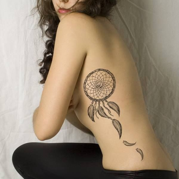 Sur les côtes : tatouage d'attrape-rêves avec quelques plumes dans Trouver une idée de tatouage d'attrape-rêve et plume indienne parmi 20 magnifiques exemples