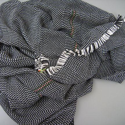 """Die Decke AmA besteht aus 100% Alpaka-Wolle und wird in der Schweiz hergestellt. Das maschienengewobene Plaid ist nach dem Slogan """"The Andes meet The Alps"""" benannt – eine schmeichelnd weiche, extrawarme und robuste Multifunktionsdecke für alle Fälle. Das schwarz-weisse Muster wird ergänzt durch eine feine Akzentlinie in Rot und Hellgrün sowie Fransen auf allen vier Seiten.  Wissenswertes über Isabel Bürgin"""