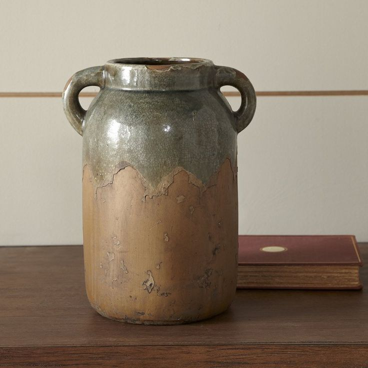 Offering a rustic vessel for cooking utensils, flowers, and more, this clay vase includes decorative arms for a folk art look.