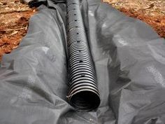 """Lay the drainage pipe in a fabric lining in the dug ditch. Place drain pipe atop fabric lining, then add gravel, covering pipe completely. Leave approximately 5"""" between top of gravel and ground surface."""