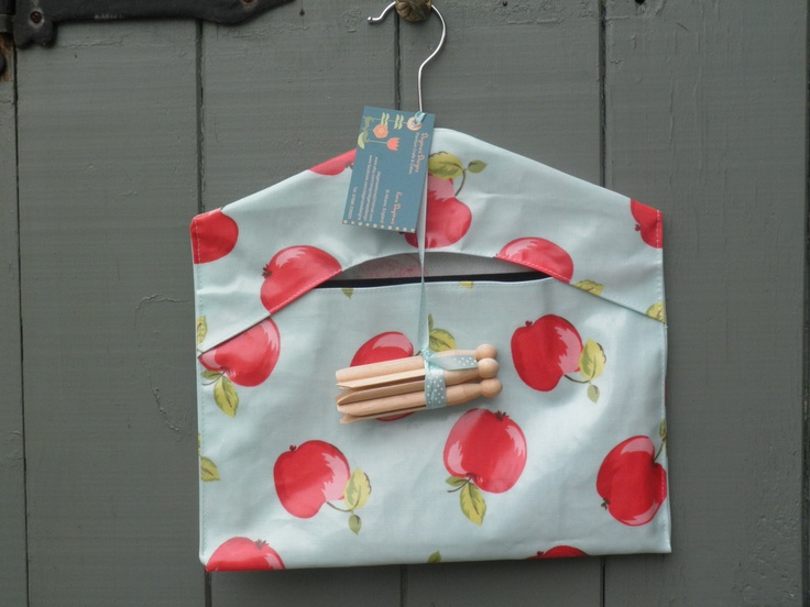 Oilcloth peg bag in retro apples print, complete with dolly pegs. Available from www.etsy.com/shop/dagenaisdesign