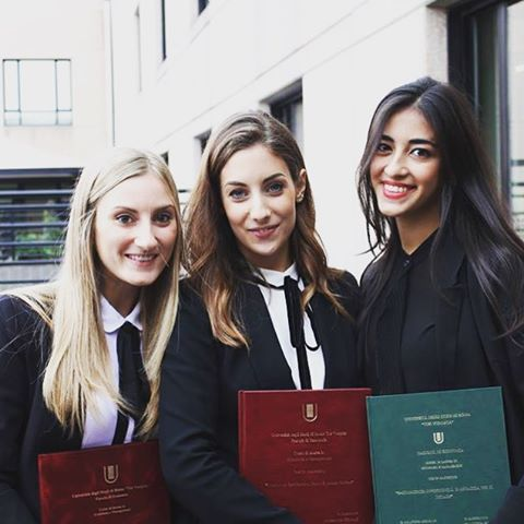 Three students of Economics at University of Rome Tor Vergata proudly showing their graduation thesis.