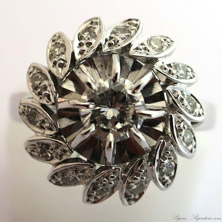 Bague fleur en or gris à châton rond centré d'un diamant brillanté en serti griffes dans un entourage de pétales obliques ornés de diamants taille 8/8.Poids estimé du diamant principal : environ 0,32 carat.Bijou d'occasion. Poinçon hibou.Poids de la bague : 3,9 g.Diamètre de la tête de bague : 14 mm.Taille 52,5 modifiable. Bague 1513-52-42-48...