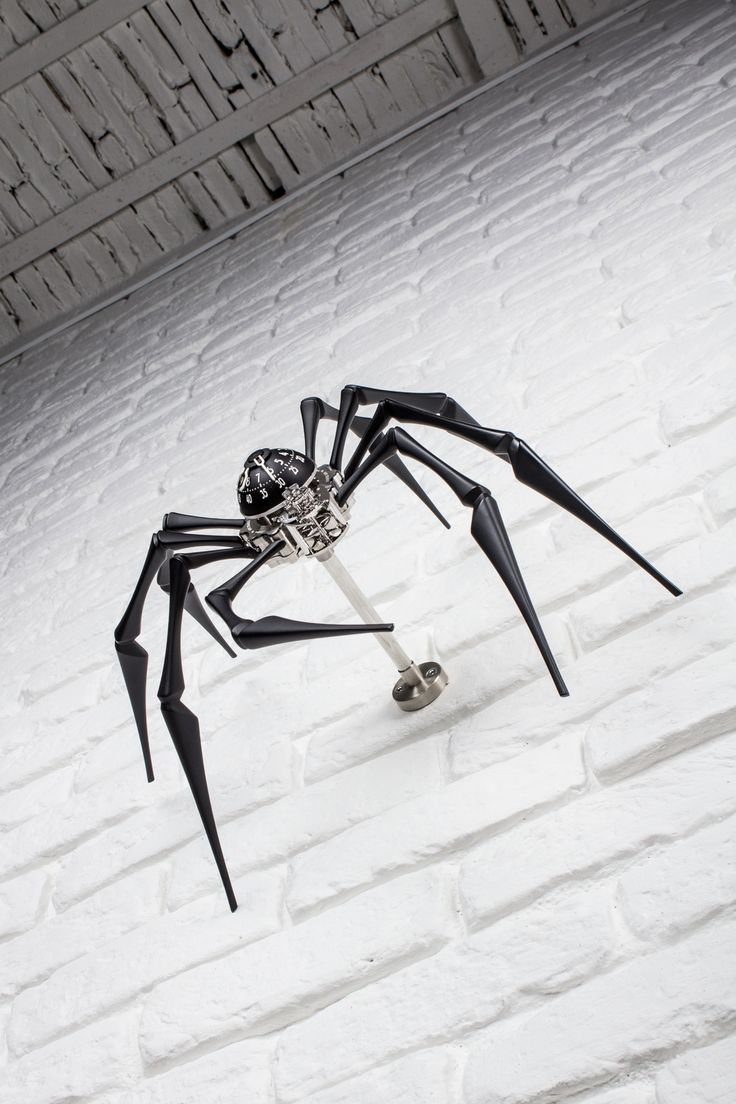 """ARACHNOPHOBIA : a """"spider clock"""" created by MB&F and L'Epée 1839, composed of 218 impeccably-finished components. The spider's head and torso is a modified L'Epée clock movement boasting a power reserve of 8 days. The body's black dome and white numerals display the hours and minutes. Attached to the abdomen are the 8 articulated legs. Those legs will make Arachnophobia stand tall on a desk… but like any spider, it can also be installed on a wall thanks to an ingenious mounting system."""