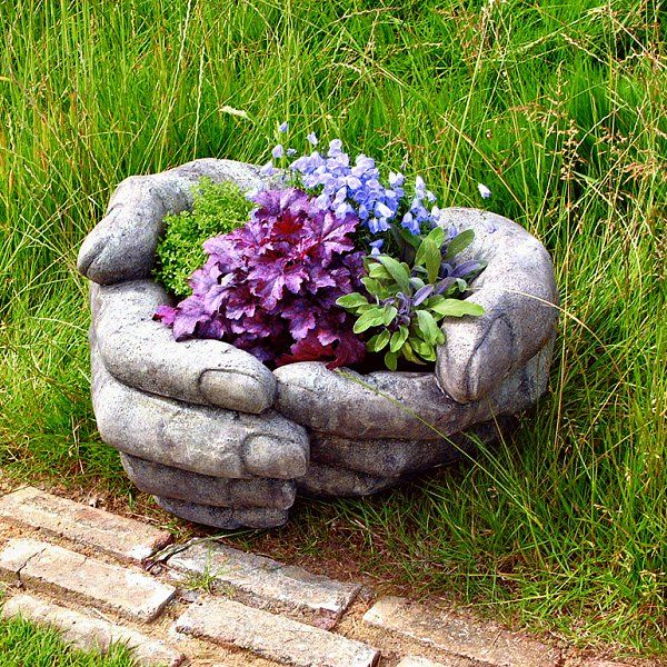 Hands Cupped Stone Garden Planter.  Could do this on a smaller scale with latex gloves and cement.  It might work,