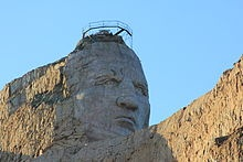 The Crazy Horse Memorial is a mountain monument complex that is under construction on privately held land in the Black Hills, in Custer County, South Dakota. It depicts Crazy Horse, an Oglala Lakota warrior, riding a horse and pointing into the distance. The memorial was commissioned by Henry Standing Bear, a Lakota elder, to be sculpted by Korczak Ziolkowski. It is operated by the Crazy Horse Memorial Foundation, a private non-profit organization.