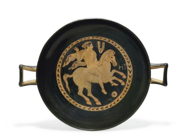 Etruscan red-figured kylix 5th century B.C. The tondo decorated with an equestrian figure, the youthful rider naked but for a chlamys draped over his left shoulder and flying out behind, right arm raised holding a spear, his horse galloping to the right, hanging fillet and stylized rosette in the field, together with two Etruscan letters 'HE', perhaps representing the name of the rider,  the exterior with band of laurel, 23.5 cm diameter without  handles. Private collection