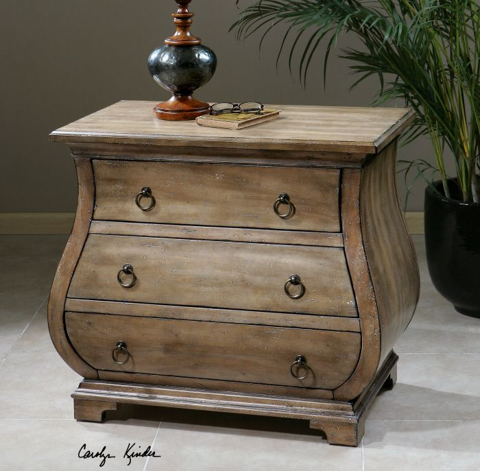 Uttermost Samina Accent Chest. Graceful bombe chest shaping with curved sides and front in sun-washed, weathered pine featuring three dovetail drawers with antiqued brass ring pulls.