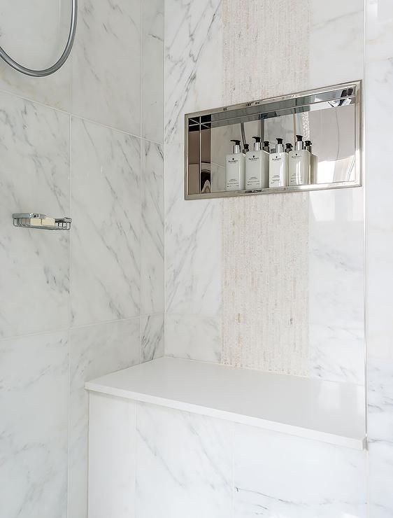 Amazing walk-in shower is clad in marble fitted with a stainless steel niche placed over a shower bench.
