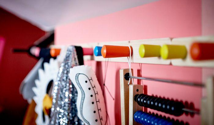 Detalle de unos juguetes y unos disfraces colgados en unos colgadores de colores…