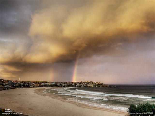Afternoon sun lights up storm clouds and rainbows over Bondi Beach