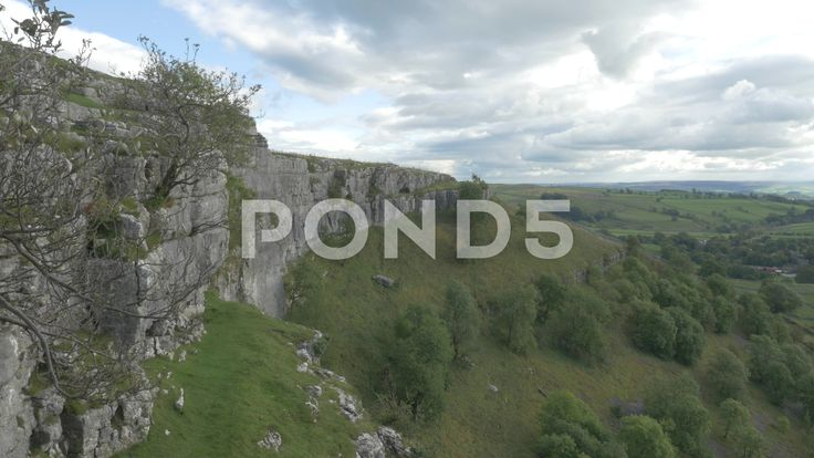 4K Climber Descending the Rock Face of Malham Cove Cliff Trees - Stock Footage | by RyanJonesFilms