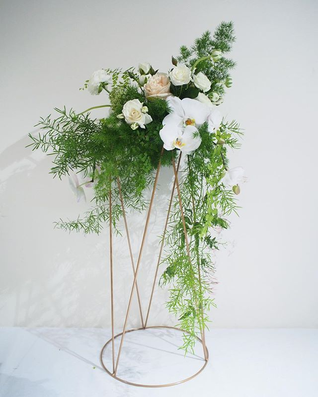 Bloodwood Botanica | Creative and unique tall floral wedding centerpiece. Made using a copper plant stand and cascading asparagus fern, white phalaenopsis orchids, roses and ranunclus