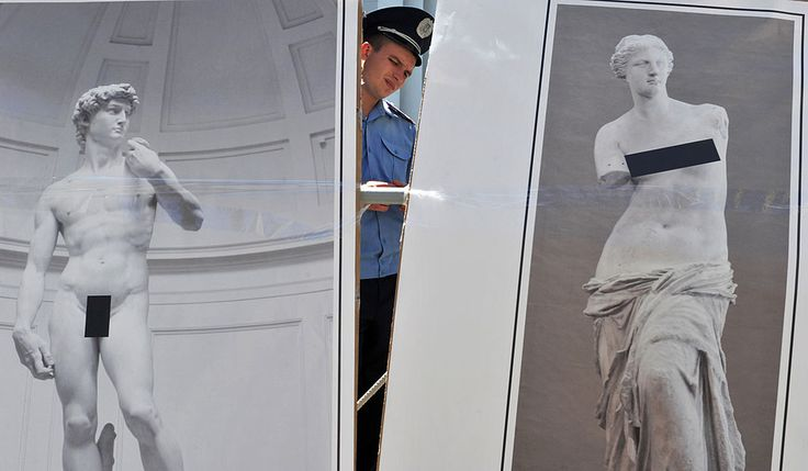 """A policeman stands guard behind placards depicting """"censored"""" masterpieces of world art during auction in front of Ukraine's President Viktor Yanukovych office in Kiev in 2011. Courtesy of SERGEI SUPINSKY/AFP/Getty Images."""