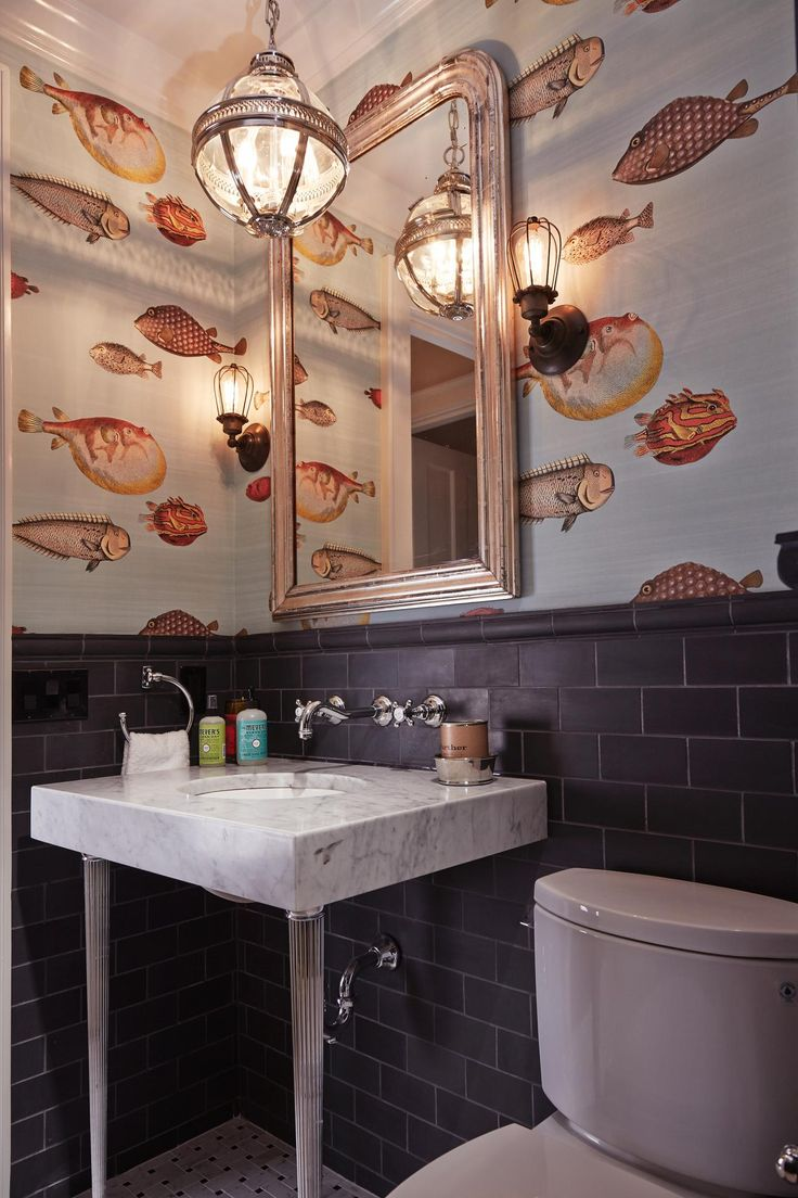 This small guest bathroom received a bold design choice: fish patterned wallpaper. The whimsical wallpaper paired with black matte-finished tiled surfaces creates a moody interior. Fornasetti Acquario at Cole & Son