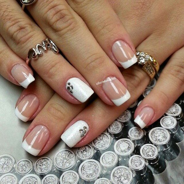 Innocent and pure looking French tips using white polish. Clear and white coats are used simultaneously as the base for this French manicure. Medium sized white tips are then lined over the clear based nails. In addition small silver beads are added unto the white colored nails for accent.