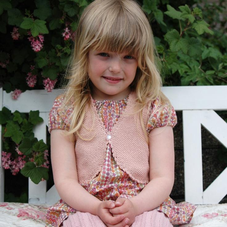 Sød pigevest strikket i den bløde pimabomuld i perlestrik og har en sød hæklet kant hele vejen rundt. Fra Strikkebogen