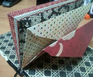 Envelope Book: from scrapbook paper, fabric, illustration board/cardboard, envelopes, and thread.