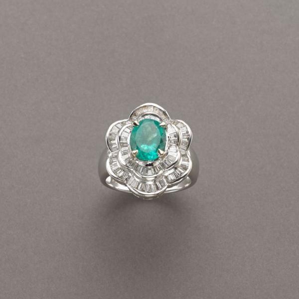 Anello in oro bianco con ondulazione concentrica di diamanti taglio tapered e a baguette ad incorniciare uno smeraldo ovale taglio composito di ct.1,90 circa, 8,60g, misura 14/54  Estimation 1.300/1.800€