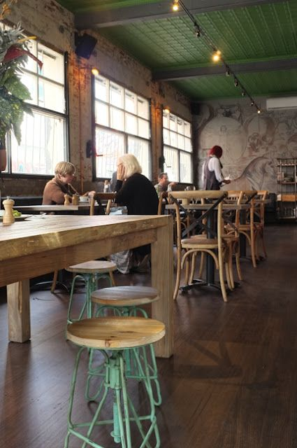Eclectic interior at Stickybeak, Melbourne. Dark timber timber floor, distressed walls, ornate green ceiling, butter blonde timber furniture & vintage mint stools.