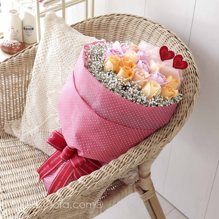 PT19 - French Kiss  Cushioned by this oh-so-French polka dots wrapper and within a protective rim of baby's breath, roses in pink, orange and champagne softly kiss your darling and poise themselves to win her heart with their flower language of love and admiration.