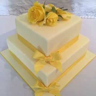 Gorgeous pastel yellow fondant wedding cake with sunshine yellow ribbon and roses to match. Perfect for a spring wedding!!