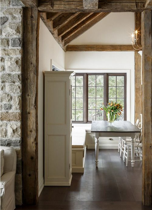Love exposed beams, natural stonework, dark wood floors, simple unadorned windows, and practical drawers under the banquette seating. Fresh flowers are a lovely natural choice. I might just change up the candelabra for something a bit more industrial like wrought iron.