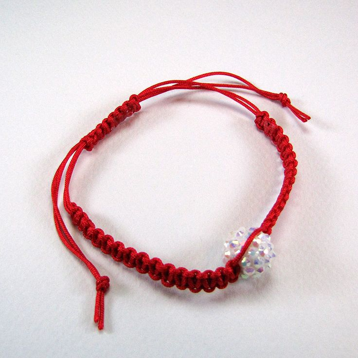 Adjustable macrame bracelet made of red cord and white resin beads.