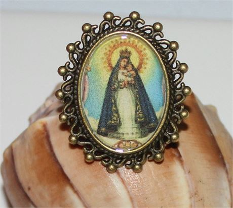 Caridad del Cobre Our Lady of Charity, bronze tone adjustable ring. large Pendant frame adjustable ring. Frame measures approx. 30mm X 20mm. Image of Our Lady of Charity under clear epoxy Water resistant, Not waterproof.   Our Lady of Charity also known as La Caridad del Cobre and is Also known as Cachita whos feast day is celebrated Sept 8th. la Virgen de la Caridad del Cobre.
