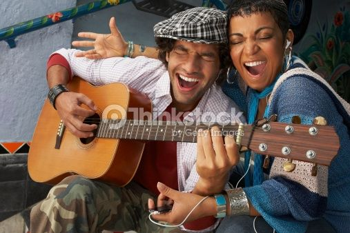 Stock Photo : Close-up of a young man singing with a young woman and playing a guitar