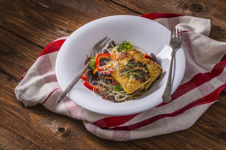 Sült tofu - mézes-szezámos üvegtésztával, fafülgombával | A különlegesen egyedi, kínai konyha egyik elmaradhatatlan alapanyaga az üvegtészta, más néven celofán tészta, ami a mungóbab nagyon finomra őrölt lisztjéből, valamint vízből készül. A mungóbab lisztje magas fehérje tartalmánál és alacsony zsír és szénhidrát tartalmánál fogva sokkalta értékesebb tápanyag, mint a búzaliszt, ennél fogva alkalmas alacsony kalóriájú étrendek kialakításához, és ami nagyon fontos, cukorbetegek is…